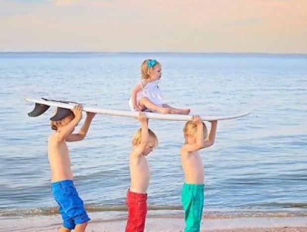 Three young boys holding a young girl on a surfboard