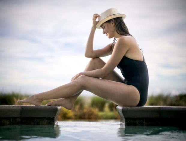 A woman sitting on a dock holding her hat.