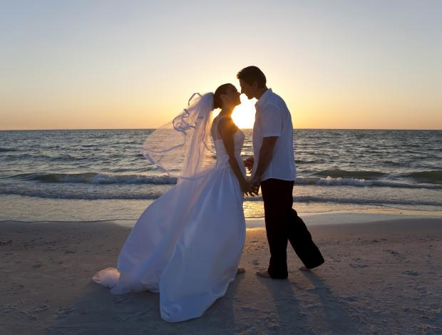 A newly wed couple kissing on the beach at sunset.
