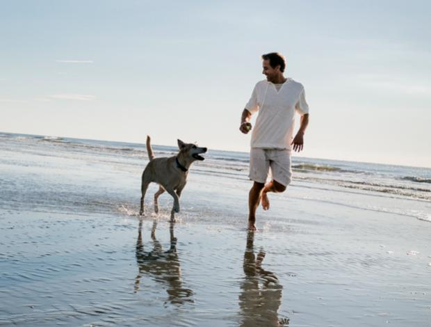 Man running with dog on beach