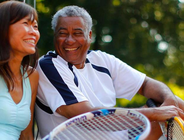 A man and woman smiling sitting on a tennis court