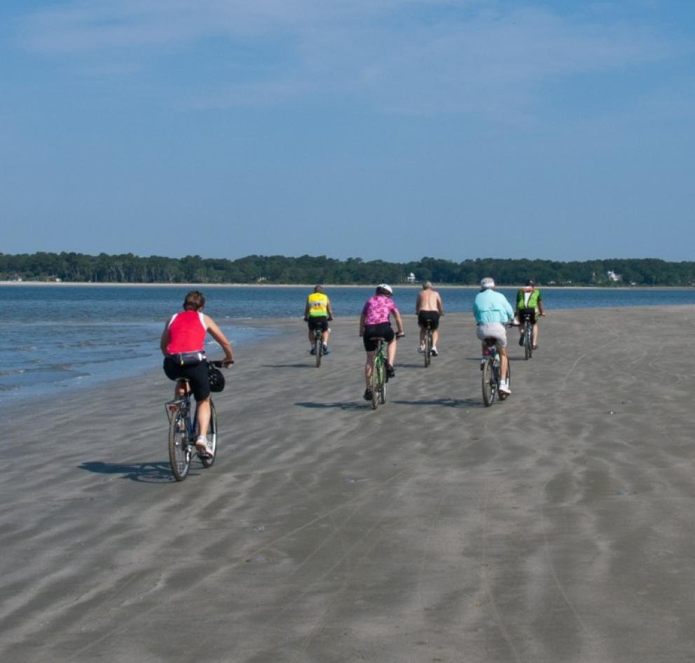 people biking on the beach