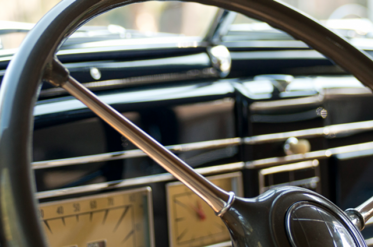 Close-up view of an antique steering wheel and dashboard of a car