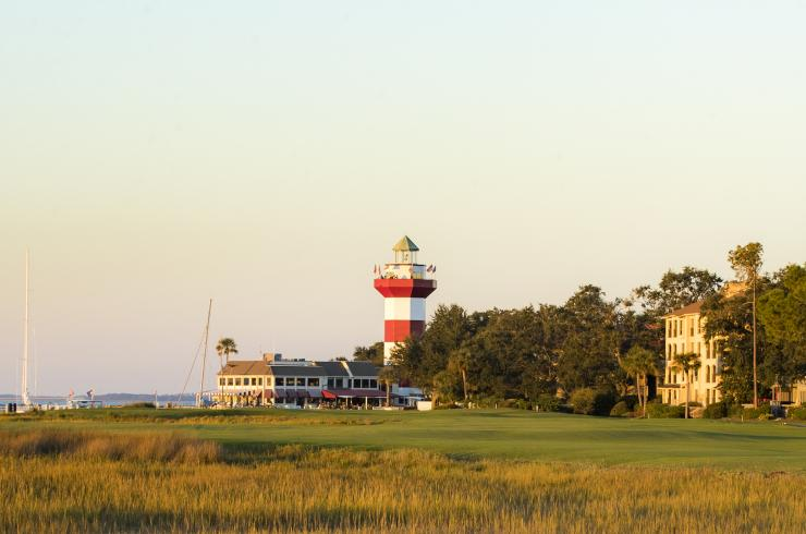 Wide angle shot of Harbour Town Golf Links with lighthouse and golfers in the distance.