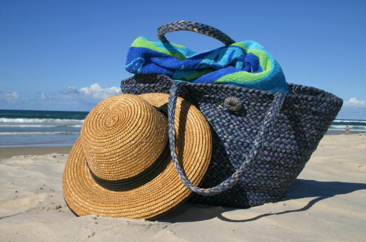 Beach bag on beach with hat
