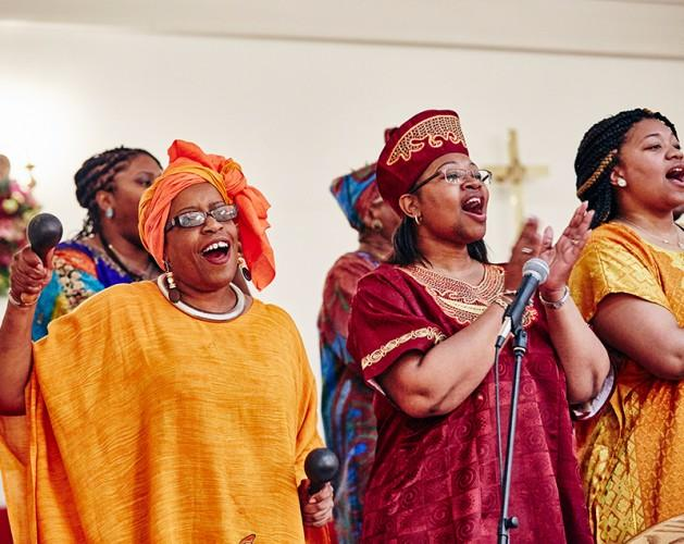 A group of women in Gullah clothing, singing