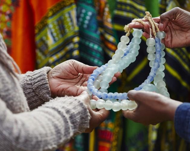 Hands holding handmade beaded necklaces