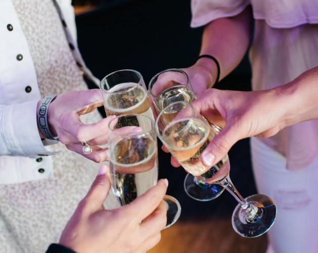 A group of people cheers-ing glasses of champagne
