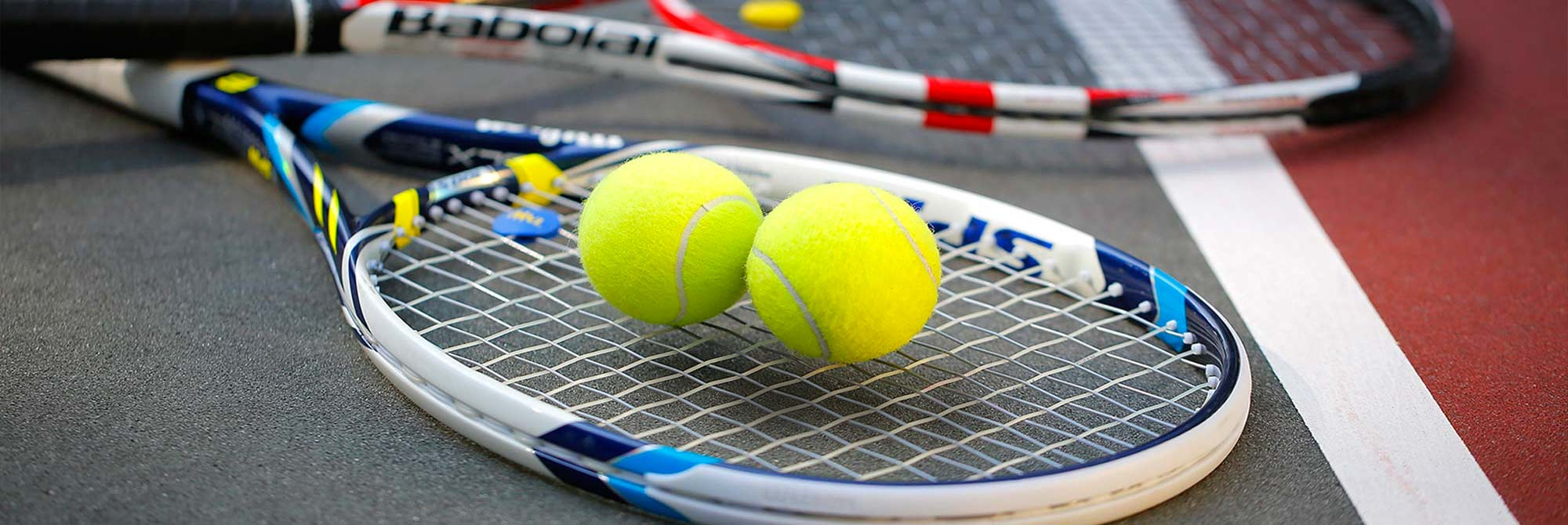 Two tennis balls resting on a raquet