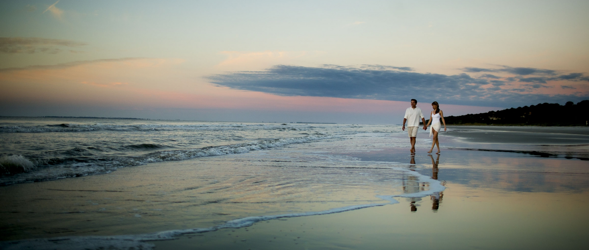 Couple walking along the beach at sunset