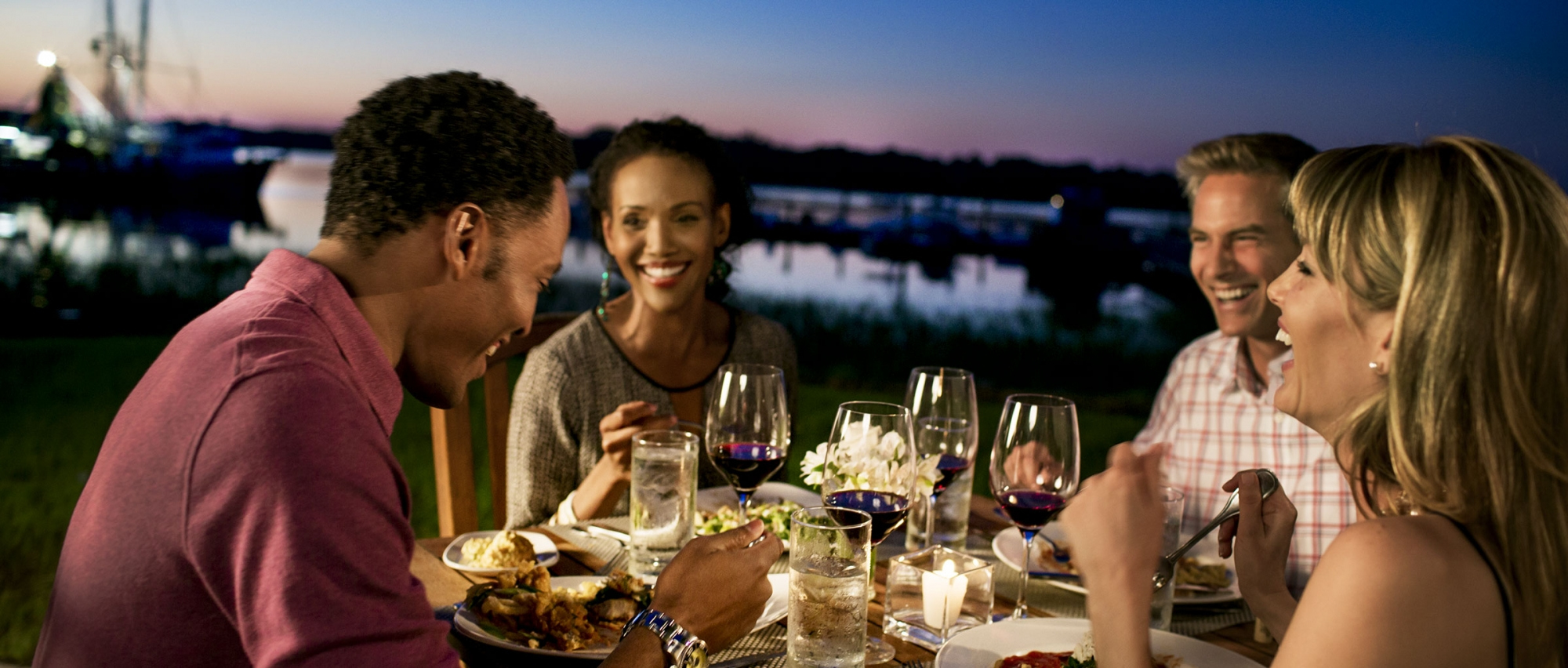 Couples dining outdoors at night near the marina