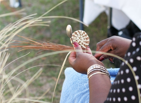 Gullah woman starting on a woven basket