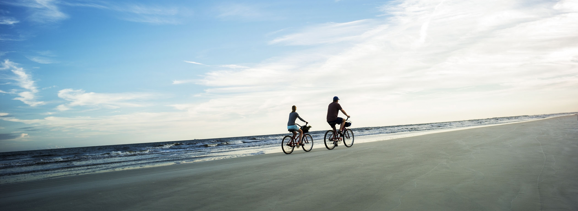 A couple riding bicycles along the beach