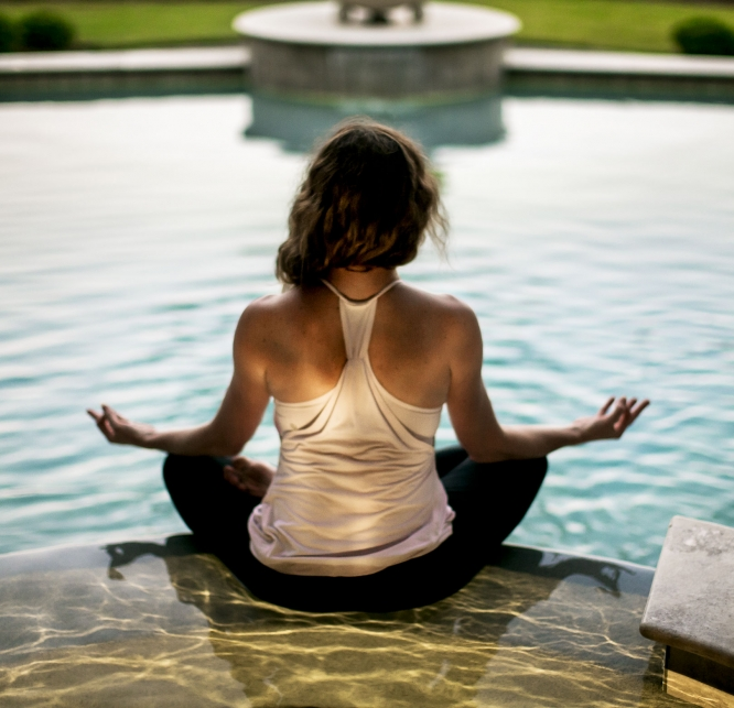 Woman meditating by a pool