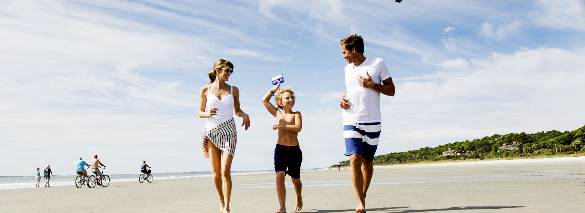 Young family flying a kite ont he beach