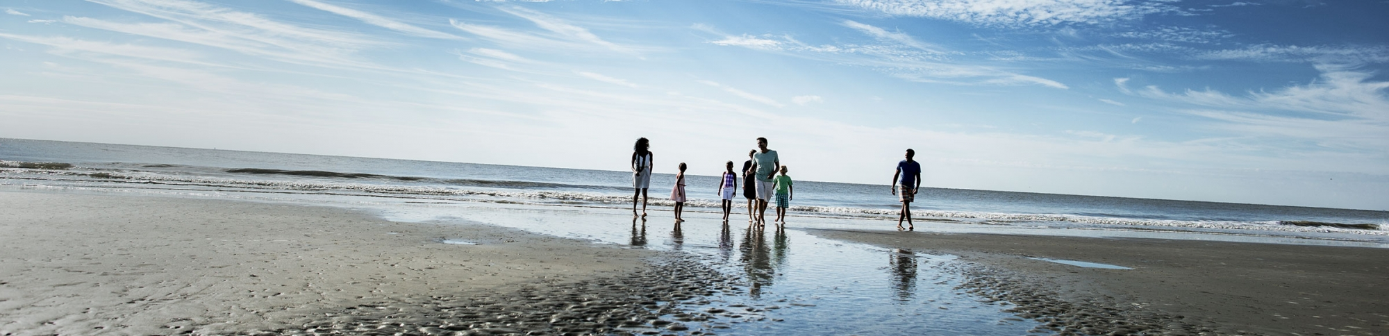 Children and adults strolling along the beach