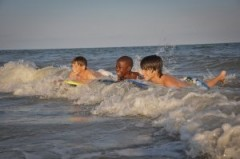 Young boys riding wave boards in the shallow waters