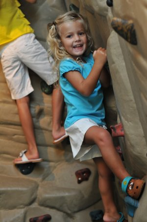 Young girl climbing the Dinosaur Rock Climbing Wall at The Sandbox