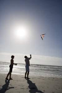 Father and son flying a kite on the beach